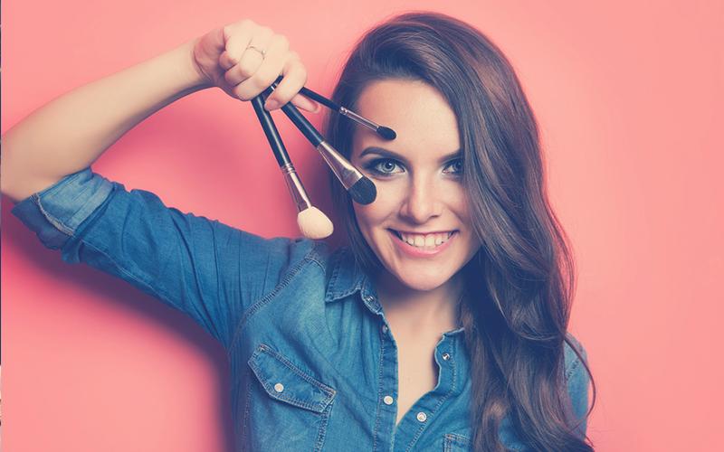Retrato de mujer con cepillos de maquillaje cerca de la cara