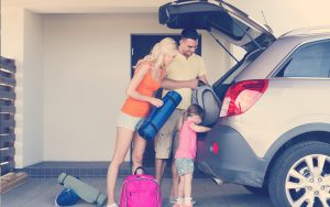 familia empacando cosas en el auto estacionado en casa