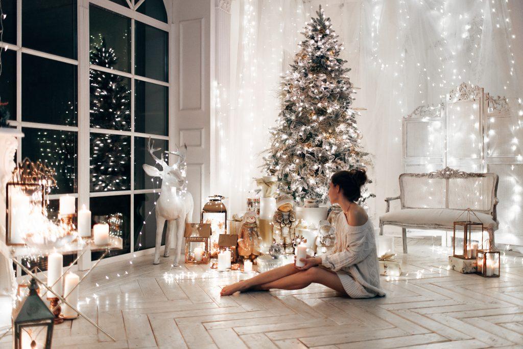 Mujer con suéter blanco, cálida y acogedora noche en el diseño interior de Navidad.