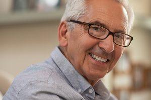 Persona mayor con gafas sonriendo ante la cámara