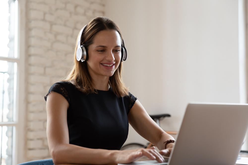 Mujer sonriente con audífonos inalámbricos trabajando escribiendo en un portátil sentado en el escritorio en el trabajo de oficina
