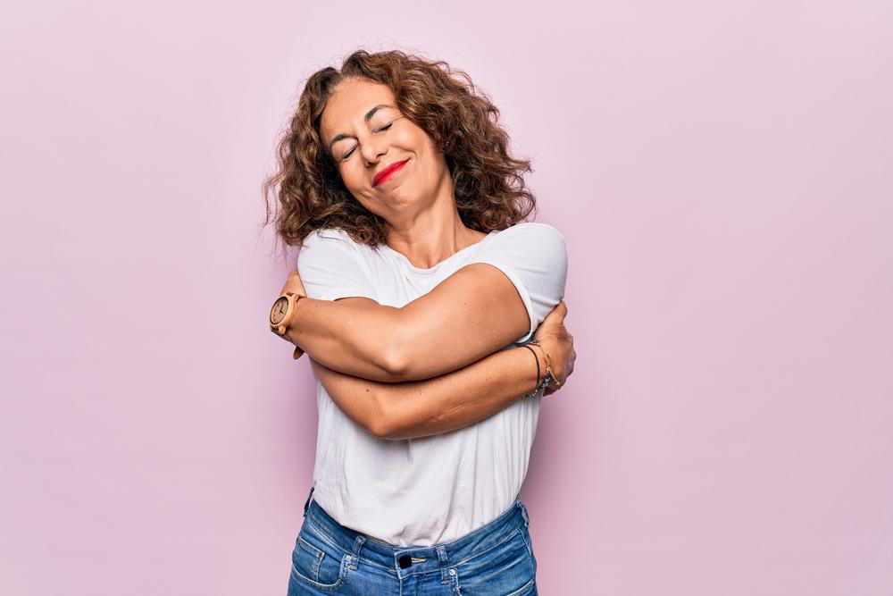 Mujer abrazándose para cultivar su amor propio