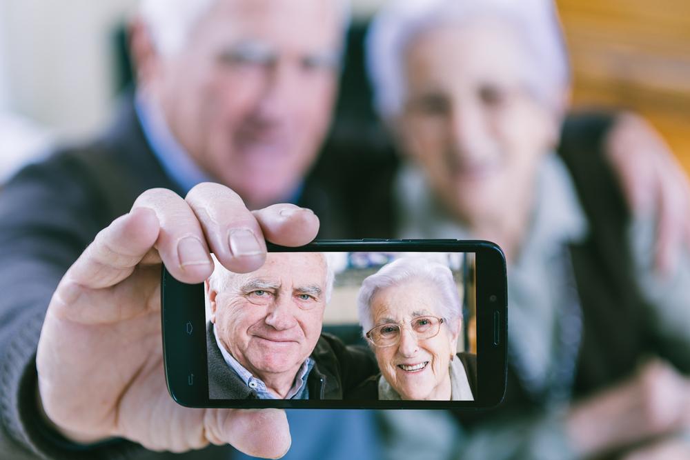 Una pareja mayor muestra una foto de autoretrato en un smartphone