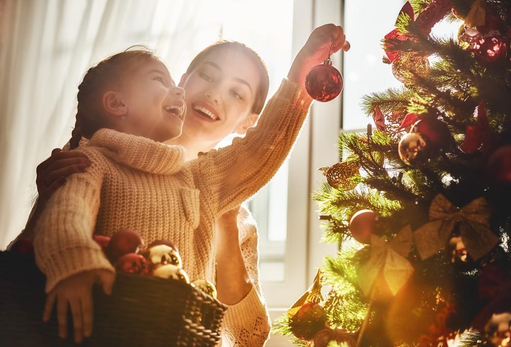 Mamá e hija decoran el árbol de Navidad en el interior
