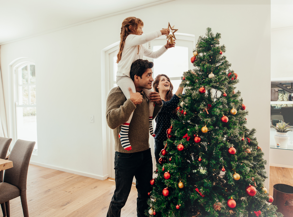 Joven con su hija en los hombros ayudándola a decorar el árbol de Navidad.