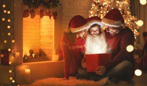 Familia compartiendo en Navidad y abriendo un regalo para su hija