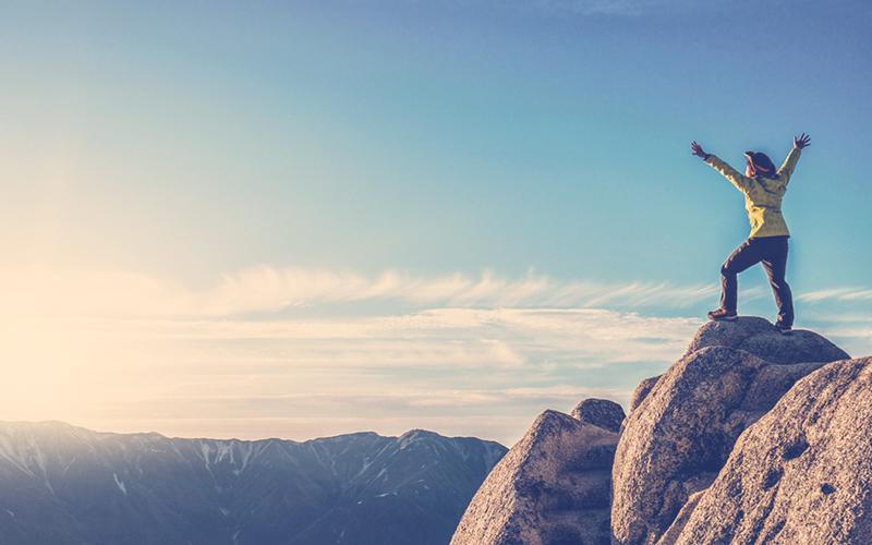 Persona llegando a la cima de una montaña