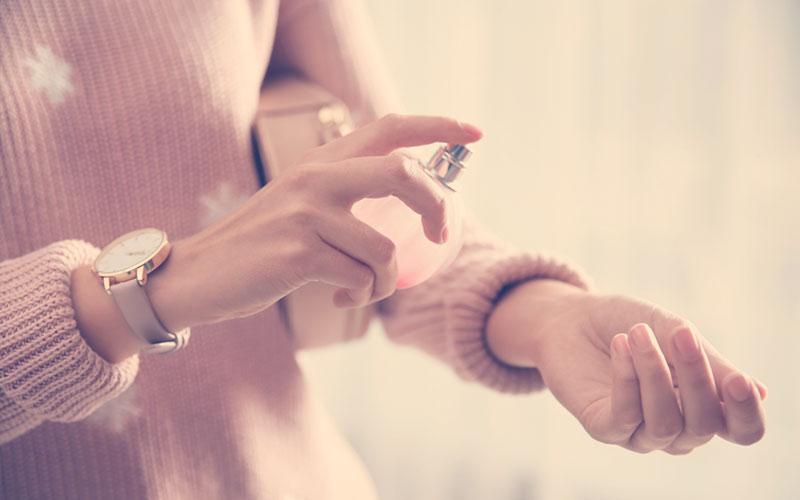 ujer aplicándose un perfume
