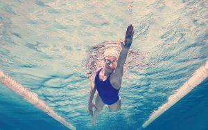 Mujer nadando y conociendo los beneficios de practicar natación