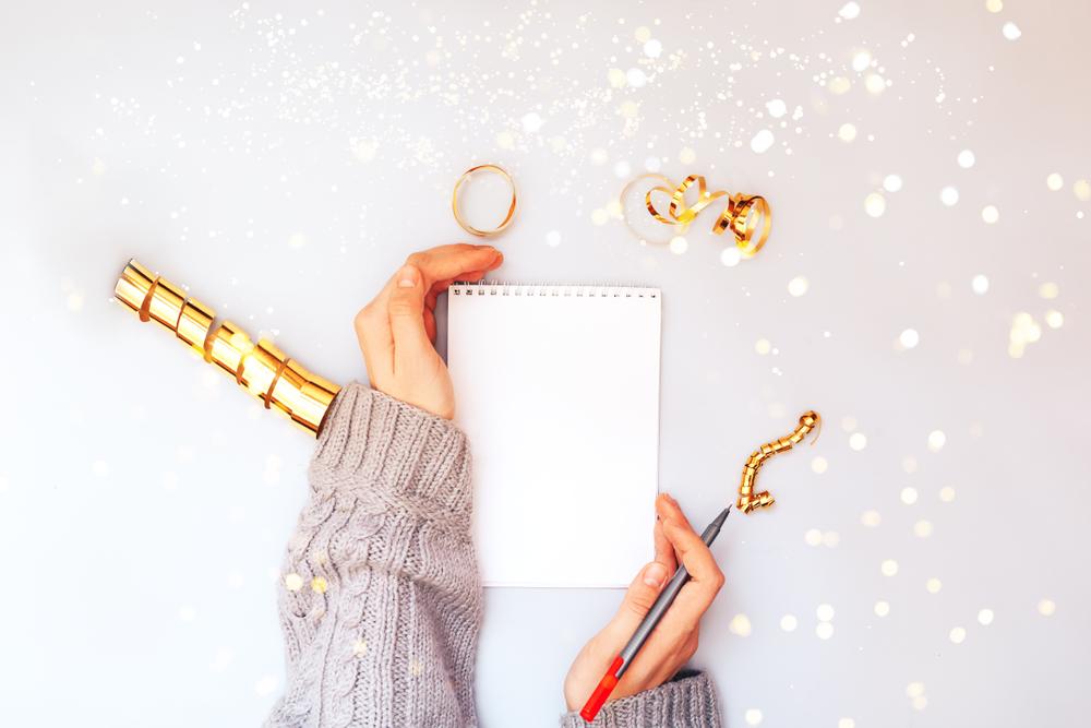 Manos de mujer sosteniendo cuaderno blanco claro, chispas doradas y escribiendo los propósitos de año nuevo
