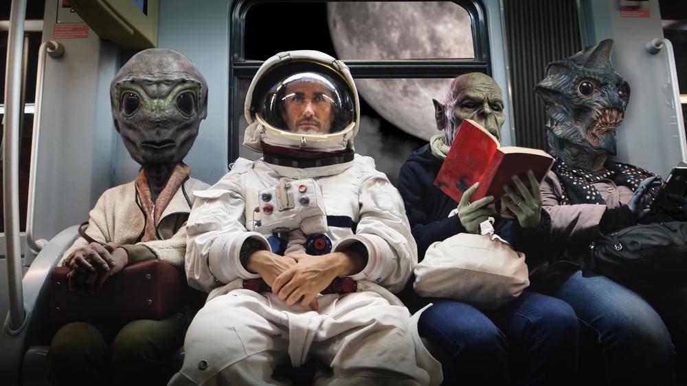 En una nave espacial, un astronauta, sentado junto a monstruos extraterrestres,