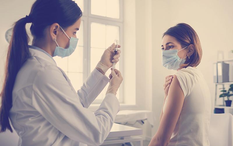 Enfermera le aplica a una mujer la vacuna contra el covid-19