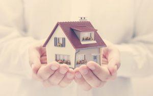 Persona sosteniendo una vivienda en sus manos