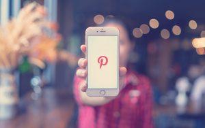 Mujer con un celular que muestra el logo de Pinterest