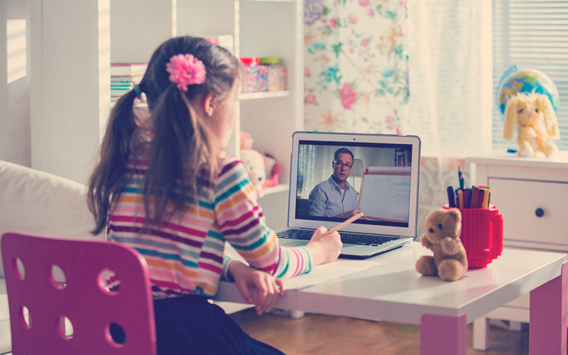 Niña estudiando y prestando atención a clase virtual