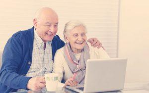 abuelos teniendo sonriendo frente a un computador