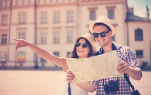 Pareja feliz revisando un mapa en un viaje turístico