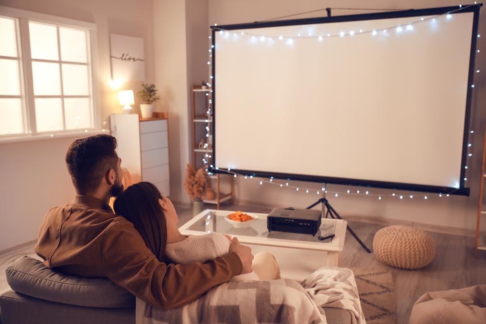 Joven pareja viendo televisión en su casa