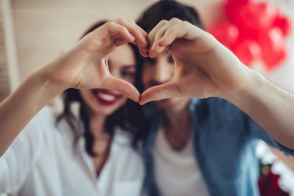 Hermosa pareja joven en casa está haciendo señas de corazón con las manos