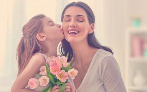 Mamá junto a su hija quien le entrega unas rosas