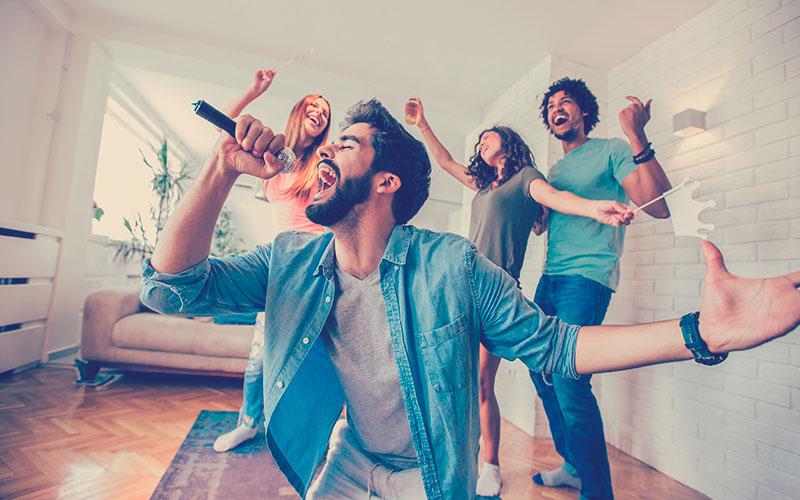 Grupo de amigos jugando karaoke en casa.