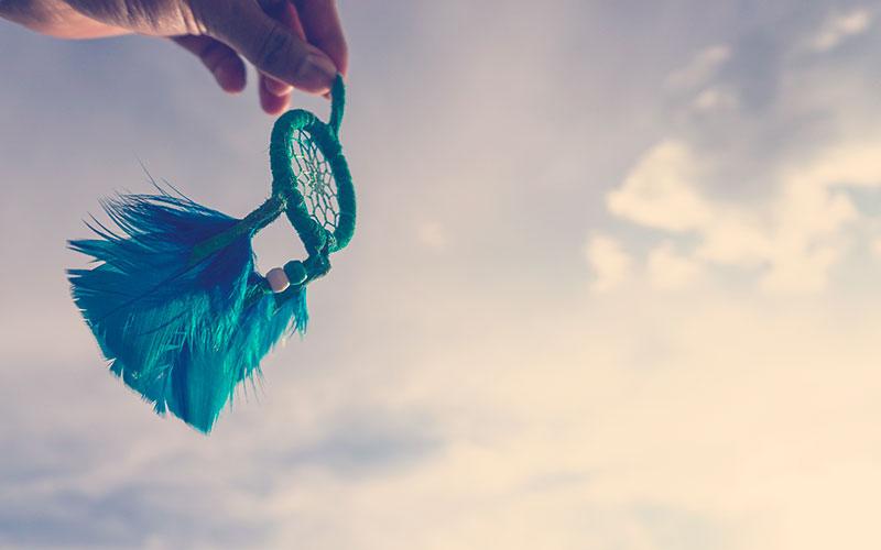 mano sosteniendo atrapasueños azul con el cielo y luz del sol de fondo