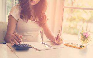 Una mujer que usa la calculadora y su nota calculan el costo en casa.