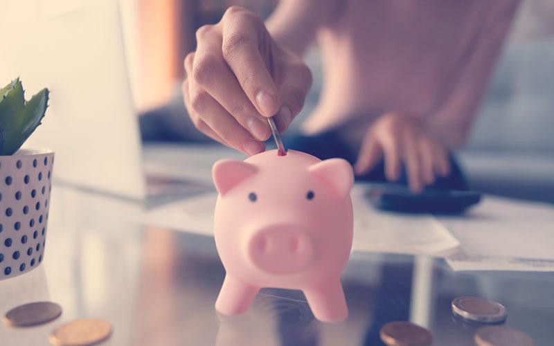 Persona ingresando una moneda en un marrano para hacer inversiones o estrategias para el ahorro personal