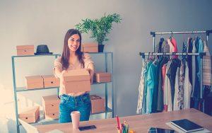Una vendedora prepara paquetes de productos para su entrega al cliente. Venta en línea o comercio electrónico