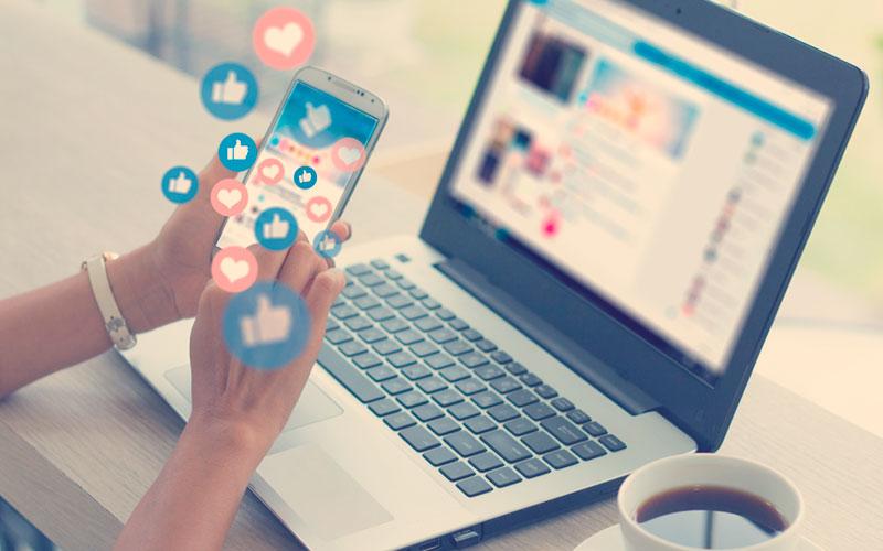 Una mujer emprendedora frente a un portátil revisando redes sociales