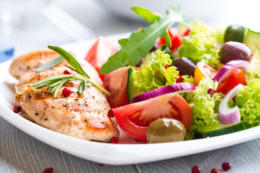 Pechuga de pollo a la parrilla con tomates, pimienta roja, aceitunas orgánicas verdes y kalamata, cebolla roja, lechuga y cohetes y romero frescos.
