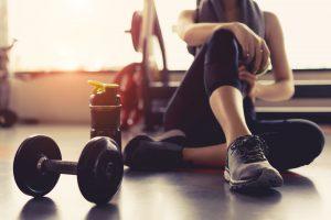 Una mujer junto con unas pesas en un gimnasio