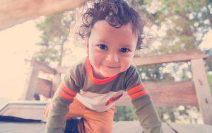 Niño con ojos grandes arrastrándose en un juego de madera en el bosque con el sol detrás