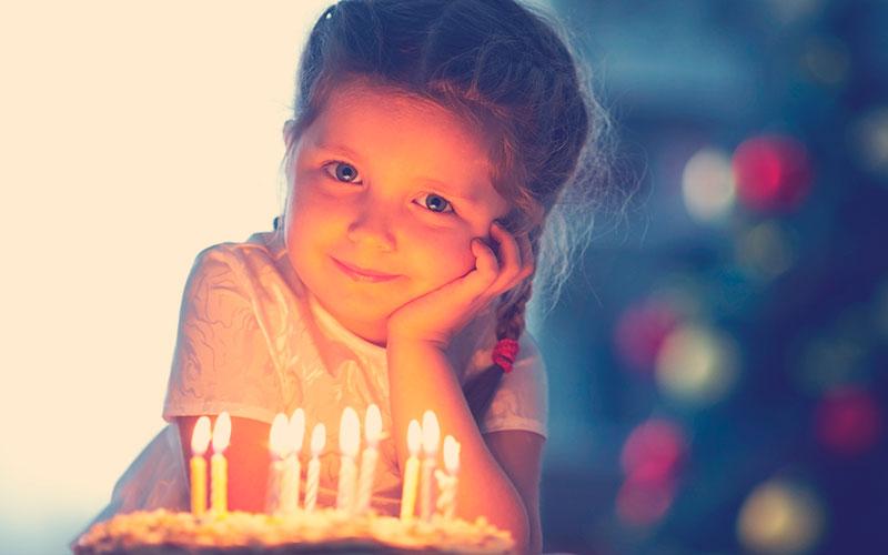 Niñas mirando a la cámara con un pastel con velas encendidas