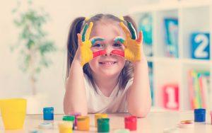 linda niña alegre mostrando sus manos pintadas de colores brillantes