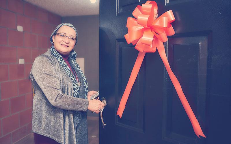 Señora feliz abriendo la puerta de su nuevo apartamento Reserva de San David, proyecto VIS ubicado en La Esperanza Sur