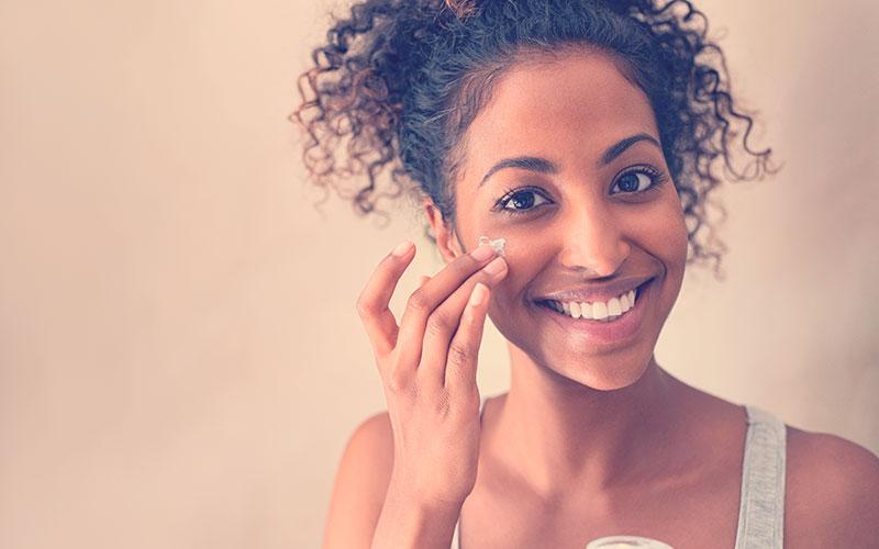 Mujer sonriente mientras se aplica una crema