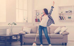 mujer feliz limpiando la casa al mismo tiempo que canta