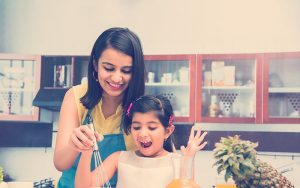 Mamá e hija preparando loncheras saludables en casa
