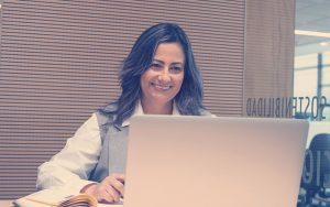 Colaboradora sonriendo frente a un computador mientras toma un curso de habilidades profesionales