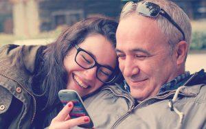Adolescente riéndose con sus padre mientras miran el móvil