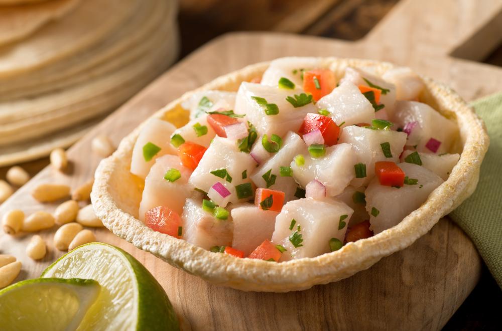 Un ceviche de pescado blanco recién hecho con tomate, cebolla roja, cilantro, pimienta roja, lima y pimienta serrano.