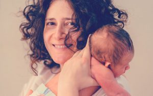 Mamá sonriendo mientras sostiene a su hijo