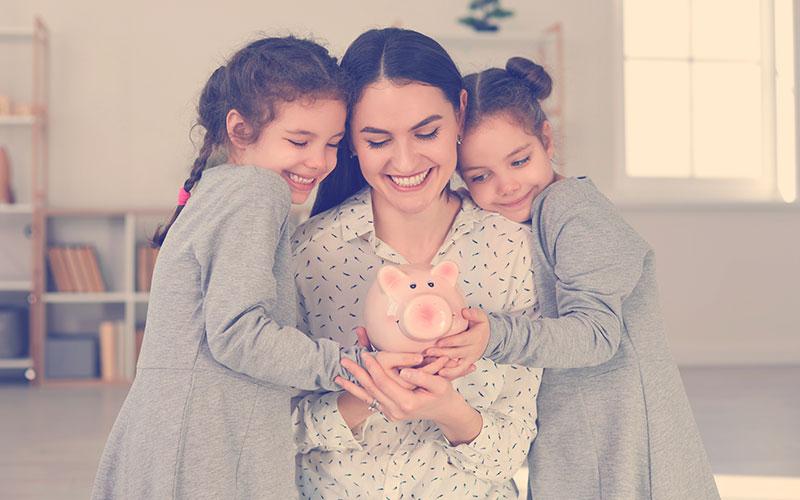 Mamá con dos de sus hijas sosteniendo un marranito para ahorrar dinero