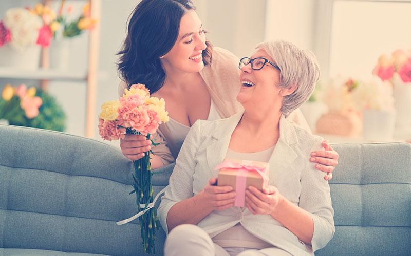 HIja regalándole flores a su mamá