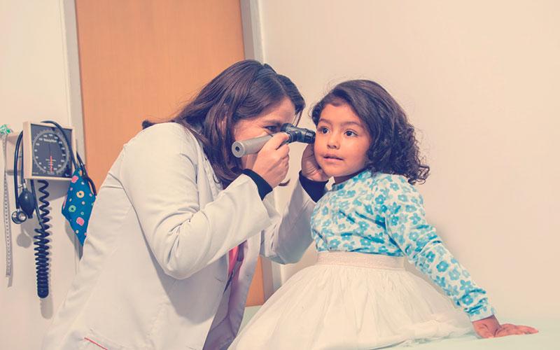 Médica revisando a una niña
