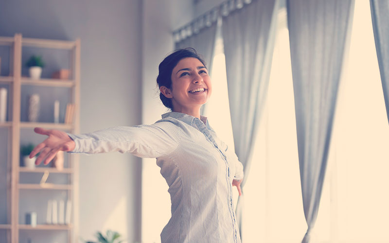 Mujer feliz recibiendo el sol desde su ventana