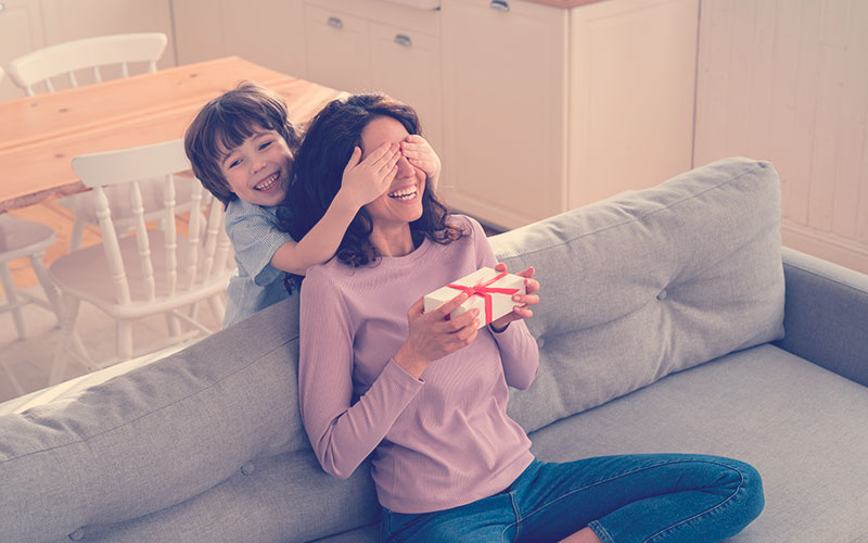 Niño sorprendiendo a su mamá con un regalo