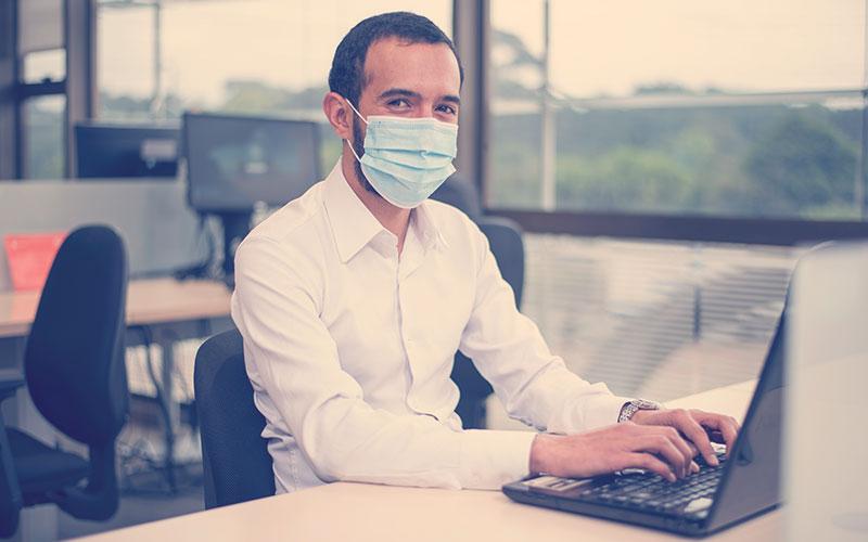 Trabajador con tapabocas en la oficina