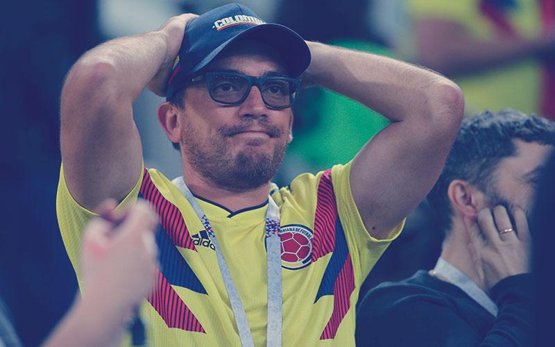 Hincha colombiano tocándose la cabeza